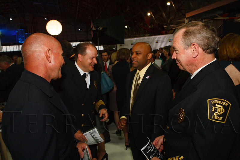 Denver mayor Michael Hancock (2nd from right) speaks with Denver Fire's Lt. Mike Somma, Eric Tate (fire chief), and Steve Garrod (division chief).  Mizel Museum 22nd Annual Gala Dinner, honoring Glenn R. Jones, at Wings Over the Rockies Air & Space Museum in Denver, Colorado, on Wednesday, May 23, 2012.<br /> Photo Steve Peterson