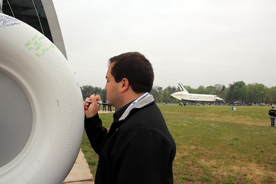 @CraigFifer signs a Space Shuttle tire to welcome Discovery, with Enterprise in the background