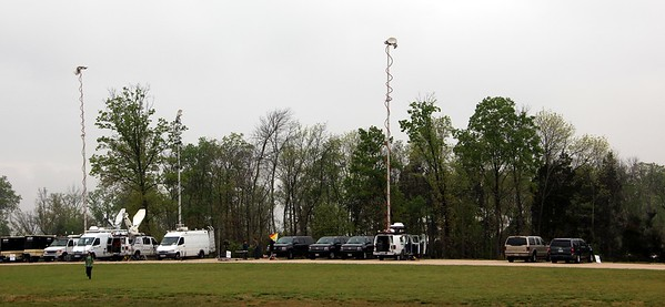 Media trucks await Discovery, while she hides behind the trees