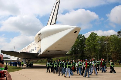 Workers from United Space Alliance follow Discovery