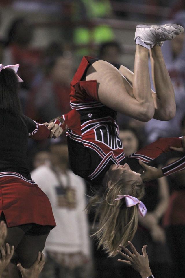 Cheerleader, Cameron Puckett, flips upside down during a pyramid stunt