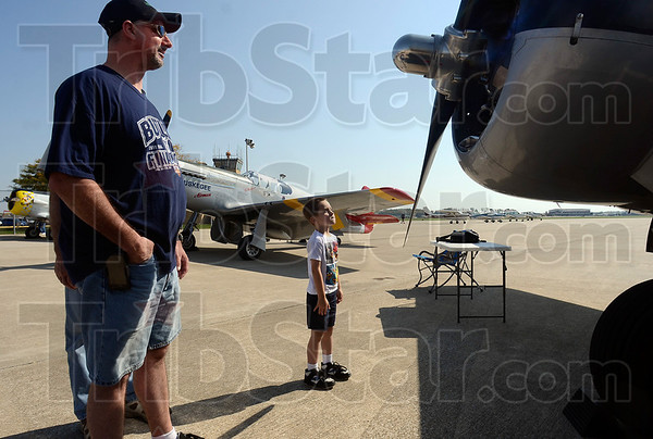 Tribune-Star/Joseph C. Garza<br /> Boy vs. propeller: Four-year-old Harrison Snoddy stares down the propeller of the C45 H as he contemplates giving it a tug as he and his dad, Wade Snoddy, left, and grandfather, Dennis Snoddy, of Clinton were checking out the vintage planes Thursday at the Terre Haute International Airport-Hulman Field.