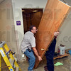 Tribune-Star/Joseph C. Garza<br /> Off the hinges: Vigo County Public Library employees Brad Hylman and Mike Sorlie remove a door from one of the meeting rooms in the basement of the library Thursday to help with the installation of new floor tile.