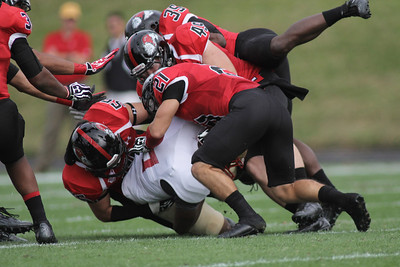 Tanner Burch (55), Brian Wittenberger (49) and Gianni Olivas (21) team up to get a tackle