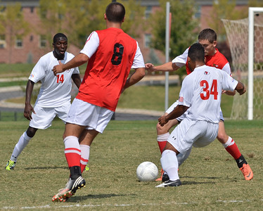 Ethan Senger (34) pushes to pass the ball to Chijioke Akujuobi (14).