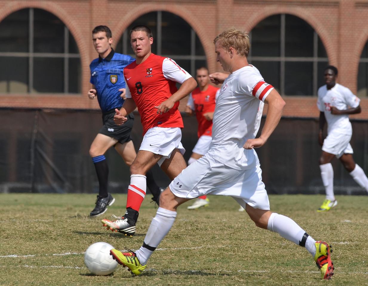 Jon Ole Reinhardsen (4) takes a long stride to pass the ball.