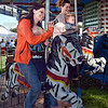 Picture this:  Kayla McIntyre checks some photos she took while riding the carousel at Sunday's Cory Apple Festival. Riding with her is Shelby Danko and her son Chace Danko. Kayla is holding Chase Counterman.