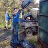 Tire toss: Indiana State University student Brandon Ping tosses a tire into the dumpster during the wetlands clean-up Sunday morning.