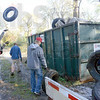 Clean-up: Several Indiana State Unversity students toss tires into a dumpster that were removed from the wetlands area along the west bank of the Wabash River Sunday morning.