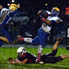 Tripped up: Carmel running back Shakir Paschall is tripped up in the backfield by Terre Haute North defensive end Alan Grayless in second quarter action Friday night on the Patriot's field.