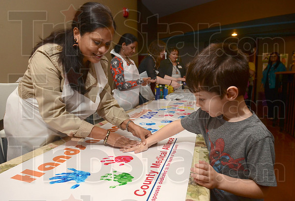 Hands are not for hitting: Sugar Grove Elementary School Kindergartener Jaydan Bologna makes his hand print with some help from Padma Shatagopam of the Vigo County Medical Alliance Wednesday at the Terre Haute Children's Museum.
