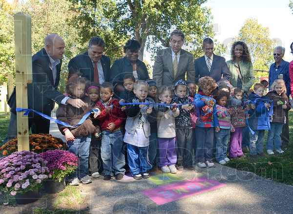 Tribune-Star/Jim Avelis<br /> Officially open: Children from Vigo County Head Start, with help from some big people, cut the ribbon opening the Born Learning Trail at Collett Park.