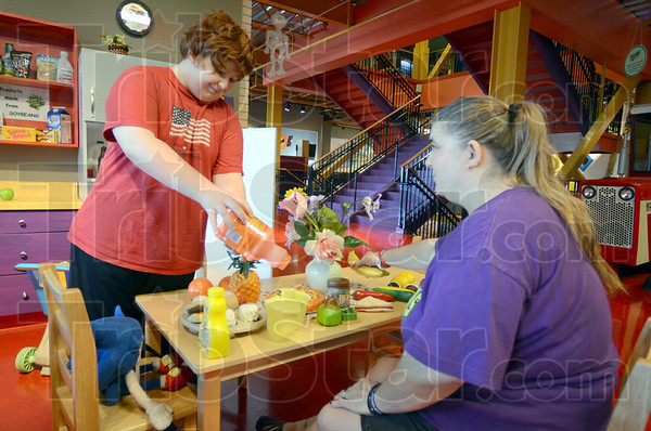 "Tribune-Star/Jim Avelis<br /> Fill it up: Timothy Montgomery ""pours"" orange juice for his mom Jodi in the display kitchen of the Terre Haute Children's Museum. They were at the museum as part of the Exceptional Explorations program of Bridges of Indiana."
