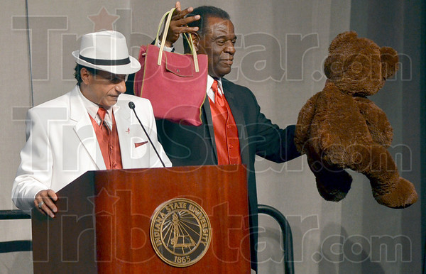 Tribune-Star/Joseph C. Garza<br /> Bid on this bear: Power of the Purse volunteer Mel Burks shows off one of the auction packages as Danny Tanoos describes each item in the set Wednesday at Hulman Center.