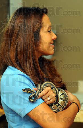 Tribune-Star/Jim Avelis<br /> Hands-on leadership: Lynn Hughes, executive director for the Terre Haute Children's Museum, holds a Ball Python, the latest addition to animals collection.