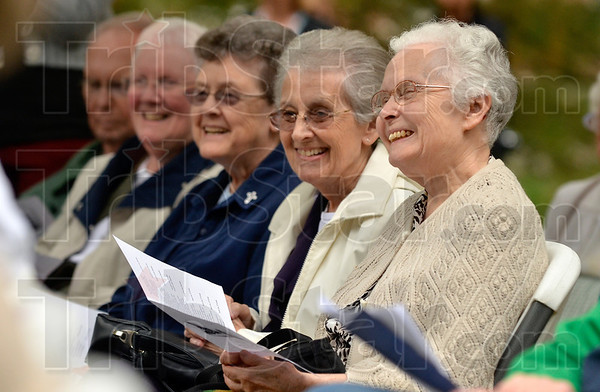 "Tribune-Star/Joseph C. Garza<br /> ""Come down sisters, we have arrived."": Members of the audience, including volunteer musician Charlotte Norris, right, smile as Sister Jan Craven reads the story of St. Mother Theodore Guerin's arrival Wednesday during the blessing and dedication of the Log Cabin Chapel at St. Mary-of-the-Woods."