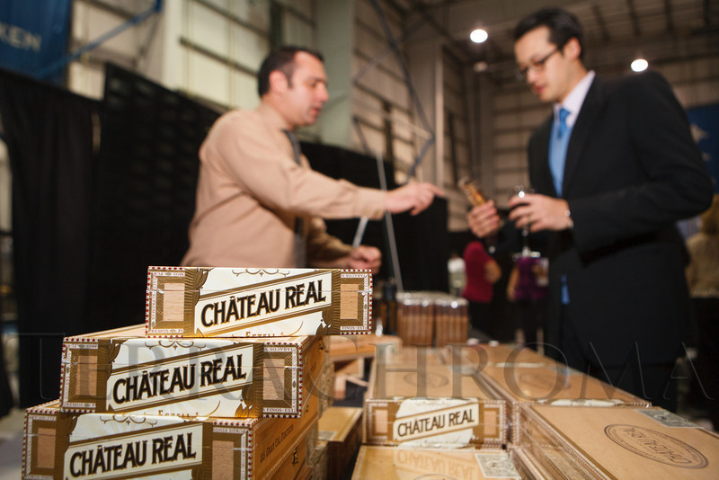Peter Roth (left), owner of the Robusto Room in Lone Tree, offered cigars to guests.  The 12th Annual Men For The Cure dinner, hosted by the University of Colorado Hospital Foundation Board of Directors and benefiting the Diane O'Connor Thompson Breast Center at University of Colorado Hospital, held at the X Jet terminal, Centennial Airport, in Englewood, Colorado, on Tuesday, Oct. 16, 2012.<br /> Photo Steve Peterson