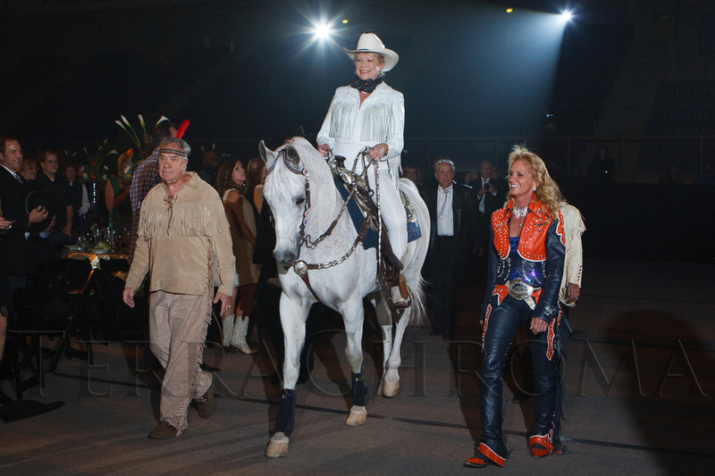 "Ernie Blake and Ann Judge-Wegner lead Thunder, ridden by Sharon Magness Blake, through the arena while the song ""God Bless the USA"" plays.  The 19th annual Western Fantasy gala, themed ""Stars Over the Rockies, Legends of the West,"" a benefit for the Colorado branch of Volunteers of America, at the National Western Events Center in Denver, Colorado, on Saturday, Oct. 20, 2012.<br /> Photo Steve Peterson"