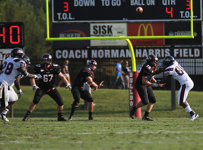 Lucas Beatty, 8 passes the ball off to a team mate. While Jamie Dunaway, 67 and David McConnell, 75 make  blocks.