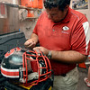 Tribune-Star/Joseph C. Garza<br /> Proper fit reduces chance of concussion: Terre Haute South head athletic trainer Scott Kidder repairs a football helmet for a student-athlete after school Thursday.
