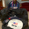 Tribune-Star/Joseph C. Garza<br /> Unpacking: Paralympic swimmer Evan Austin unpacks his swimming caps and team uniform Thursday at his home in Riley.