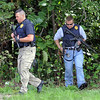 Search: Two heavily-armed Terre Haute police officers check a wooded area near 10th and Poplar Streets Friday afternoon during a search for a robbery suspect.