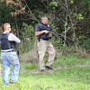 Perimeter: Two Terre Haute police officers provide perimeter security as a police K-9 team searches a wooded area near the scene of Friday's robbery.