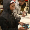 Tribune-Star/Joseph C. Garza<br /> In comparison: Indiana State University student Alexis Johnson of Portage compares her phone with the new iPhone 5 as fellow student Jaden Joshua of Merrillville looks over a new model himself Friday at Verizon Wireless.