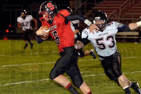 Tribune-Star/Joseph C. Garza<br /> Not afraid to run: Terre Haute South quarterback Danny Etling runs for yardage as he avoids the tackle by North Central's Kirk Harlow during the Braves' game against the Panthers Friday at South.