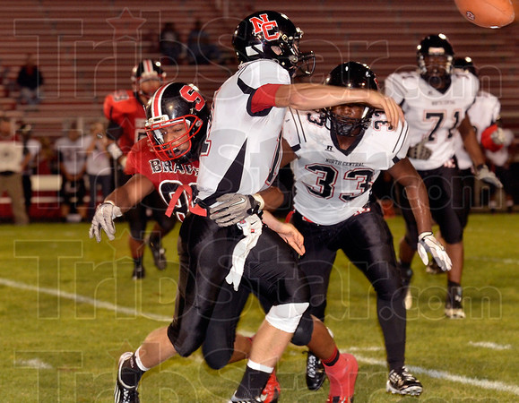 Tribune-Star/Joseph C. Garza<br /> Keep up the pressure: Terre Haute South's Howie Lawson puts a hit on North Central quarterback Michael Loggan in the first half of action Friday at South.