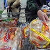 Tribune-Star/Jim Avelis<br /> Bread line: A hand reaches for a package of bread at the Catholic Charities Bread and Produce market early Saturday morning. Free bread and produce are offered there each month.