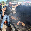 Chops: Brandy Jackson raises the lid on his grill to check the progress of his cooking meat Sunday at the Cory Apple Festival.