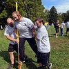 Tribune-Star/Joseph C. Garza<br /> One step at a time: Brandy Bridgewater of White Construction tries to complete a lap on stilts with the help of co-workers Tony Wyrick and Michael McMullen Saturday during the First Financial Corporate Olympics at Forest Park.