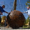 "Tribune-Star/Joseph C. Garza<br /> Heavy lifting required: Indiana State University construction manager Steve Culp and Misco President Steve Durham hold Brandon Zebold's ""ISU Sphere"" in place as they prepare to tether straps to the piece to lift it Wednesday on the university's campus."