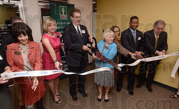 Tribune-Star/Joseph C. Garza<br /> A cut above: Ann Valentine, chancellor of Ivy Tech Community College-Wabash Valley, cuts a ribbon with Mayor Duke Bennett during a ceremony to open the new Martin Luther King, Jr. Center in the Meadows Shopping Center Wednesday, Aug. 29.