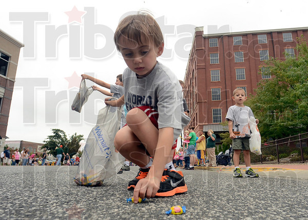 Tribune-Star/Joseph C. Garza<br /> Prosperous parade: Treydon Hunter, 6, scoops up a few pieces of bubble gum during the Labor Day parade Monday on Wabash Avenue.