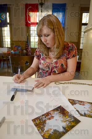 Tribune-Star/Joseph C. Garza<br /> A few words of encouragement: Elizabeth Coley, associate director of campus life at St. Mary-of-the-Woods College, writes a note for a military member on a Thank You card Tuesday in LeFer Hall.
