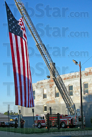 Tribune-Star/Sheila K. Ter Meer<br /> Brazil firefighters use the city's ladder truck to fly a huge American flag at half staff Tuesday morning outside City Hall in observance of 9/11.