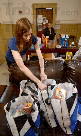 Tribune-Star/Joseph C. Garza<br /> For the ones over there: Malia Mohan, coordinator of campus ministry at St. Mary-of-the-Woods College, places a care package in a satchel Tuesday in the Le Fer Hall's military resource area. In the background is Kim DisPennett, administrative assistant for academic affairs.