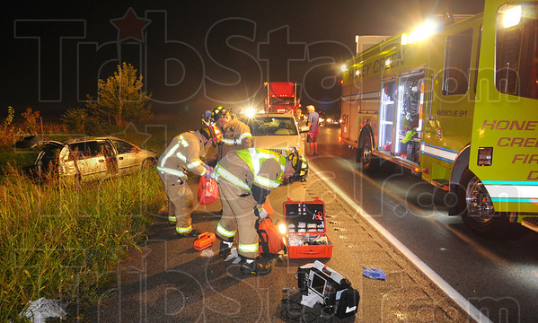 Tribune-Star/Jim Avelis<br /> One vehicle: Emergency personnel clean up their gear at the scene of a one vehicle accident Tuesday night. A north-bound grey minivan left the east side of Indiana 41 just south of Dallas Drive. One person was injured.