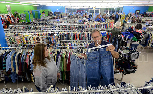 Tribune-Star/Joseph C. Garza<br /> Decisions, decisions: Goodwill customer Brent Sanders compares two pairs of jeans after the grand opening of the store in Sullivan Tuesday. With him is fellow customer, Kayle Johnson.