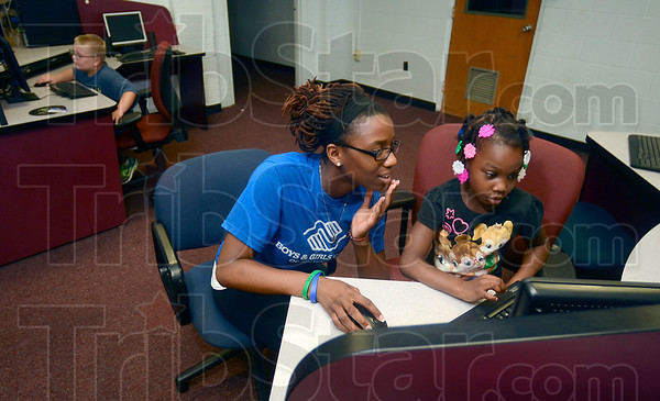 Tribune-Star/Joseph C. Garza<br /> Building skills together: De'rricka Owens, right, 4, works with Terre Haute Boys & Girls Club staff member Shamerria Taylor in the club's technology center as Cain McKee, 6, tries his hand at computer design Tuesday in the former Chauncey Rose Middle School. Tayor is an Indiana State University student from Indianapolis.