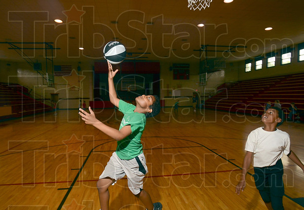 Tribune-Star/Joseph C. Garza<br /> Taking the court: T.J. Baker shows off his hoop skills as he makes a reverse lay-up while playing basketball with Dominique Riley Tuesday at the new Terre Haute Boys & Girls Club in the former Chauncey Rose Middle School.
