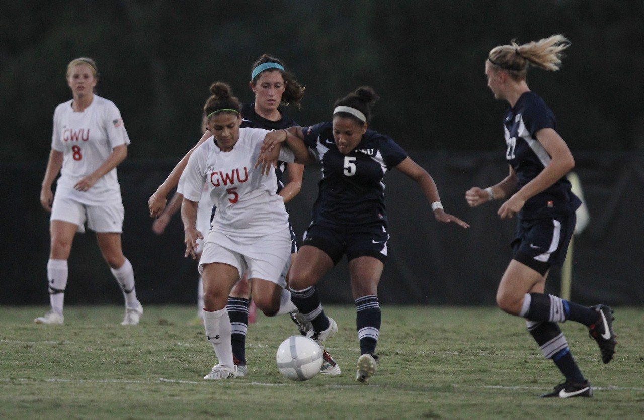 Ele Margelos (5) fights against two Charleston Southern players to keep possession of the ball