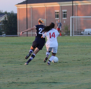 Karyn Latorre (14) pushes past Charleston Southern's player.