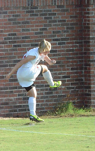 Shelby Hooe (16) puts all of her effort into her corner kick in the first quarter.
