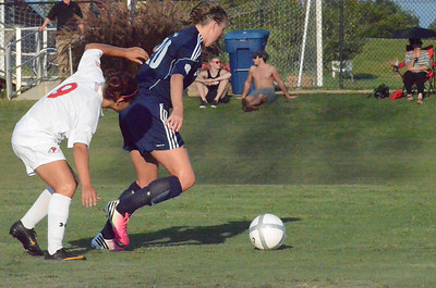 Samantha Gutierrez (9) pushes to get through to the ball from the opposing player.