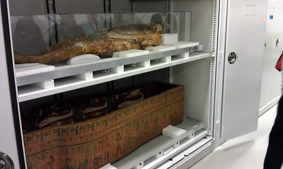 On the top shelf, the corpse of a Philadelphia man whose body fat turned into soap as a result of ground water leaking into the coffin.  On the bottom shelf, a coffin from Egypt, circa 500 BCE