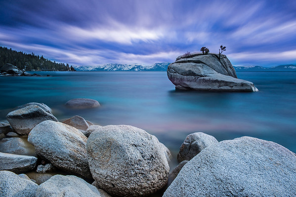"Ever since I first saw David Shields photos of Bonsai Rock I had wanted to shoot this location. For the past couple years I've leased a ski cabin with several of my friends for the entire winter. Being so close to Lake Tahoe and Bonsai Rock you'd think it would be easy to get here to shoot. Last year I had made it up to the eastern shore to photograph Bonsai but I waited too long into the year (it was almost May when I made my way over there) and the sun was setting more northerly than I wanted. Willie and I decided to do a Tahoe photo weekend at the end of March, hoping the sunset would still be south-westerly enough for a nice sunset. It was storming all week and we rented a 4 wheel drive SUV for the trip. Hoping to get a great sunset we departed plenty early from my cabin and arrived at Bonsai Rock pretty hopeful.  Random side-story: I've driven all over California (and many parts of the United States) over the past 6 years and although I've seen ""Caution: falling rocks"" signs, I've never actually really paid attention to them or had any issues. On the drive to Bonsai Rock the car in front of me rolled down his window and started waving his arm, pointing to the left, signaling something that I couldn't figure out. He quickly changed lanes and that's when I realized what he meant …. GIANT F'ING BOULDER!!!!!!! There were 3 cars to my left and I had to slam on the brakes to avoid hitting the giant rock. This thing would have seriously messed up the SUV. So Mr. Car in front of me … thank you!   We arrived at Bonsai Rock with plenty of time before sunset. Last year there was so much snow that the lake level rose fairly significantly. Even with a dry winter the lake level is much higher than we really want for good Bonsai Rock photos. The beautiful foreground rocks are mostly under water. Willie and I spent a couple minutes looking at compositions but with so few rocks exposed we were pretty limited and found our shots pretty quickly.   We had plenty of time to kill before sunset and it was partially cloudy so I decided to pull out the Lee Big Stopper and see what kind of effect I could get. I set up a 3.5 minute exposure, clicked the button and sure enough, I got a super neat pattern in the sky. The water was pretty choppy and the long exposure turned the water into glass. Perfect! Now we just need a beautiful sunset and I'll repeat this. Unfortunately we didn't get a sunset (thick clouds blocked the sunset) but I did manage to get a nice long exposure photo!   Nikon D700 w/Nikkor 24-70mm f/2.8G ED AF-S: 36mm, f/16, 3 min 20 sec, ISO 200 Lee Filter Holder + 0.6 HiTech Soft ND Grad + Lee Big Stopper"