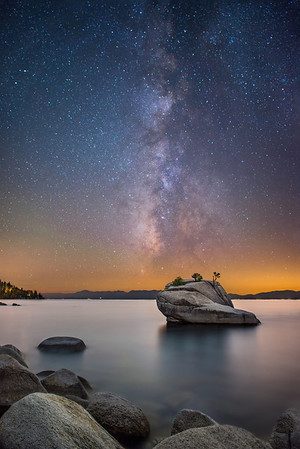 One of the challenges in photography is to find something that nobody else has taken a photo of. Around the Bay Area there are so many amazing photographers that it's very difficult to find a scene that they haven't already photographed! One of my favorite places in Lake Tahoe is the iconic Bonsai Rock. I first saw this place a couple years ago when David Shields uploaded a couple shots from here and I knew I had to go to the place!   One photo that Willie and I had never seen was a photo of the milky way over Bonsai Rock. We did some research and decided that we would head to Tahoe on August 16th. Unfortunately for us, a couple other photographers must have read our minds because almost less than week before we were scheduled to head to Tahoe a couple photographers took the exact shot we were going to take!   After a long day at work in which we were both exhausted, we left the Bay Area and I drove up to Tahoe and over to Bonsai Rock. We arrived early, hoping to light-paint the rock before the milky-way was in position. Quickly we realized that light-painting gave a fake looking view of Bonsai Rock and the tree on top. After photographing the Milky Way sitting on-top of Bonsai Rock we proceeded to take several minute long exposures taking advantage of the natural light to show Bonsai Rock in our photos. Luckily there was enough light pollution to provide a nice orange glow in the background and also light up the rock.  This is a 3-shot blend: an 8-minute exposure to show Bonsai Rock, a 15 second exposure of the Milky Way above Bonsai Rock, and a 6 minute exposure for the foreground rocks framing the bottom left of the photo  Nikon D800 w/Nikkor 24mm f/1.4G ED: Milky Way: 24mm, f/1.6, 15 sec, ISO 3200 Bonsai Rock: 24mm, f/2, 8 minutes, ISO 640 Foreground Rocks: 24mm, f/2, 6 minutes, ISO 400